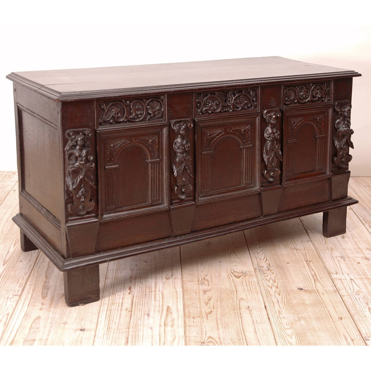 Composed of antique architectural elements which include carved female figures, arabesques and arched panels, this hinged chest made of oak has a dark and rich patina. Some of the elements appear to be from the 1700s or earlier. Lovely for use at