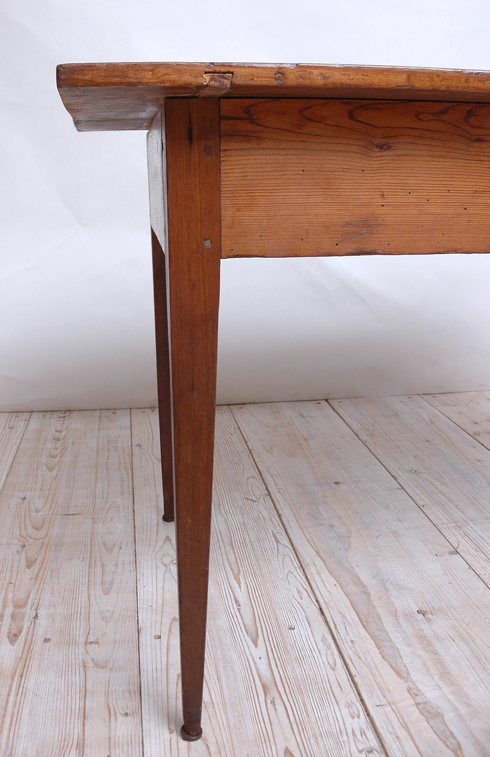 A multipurpose farm table in pine with square-tapering legs. Features mortise and tenon pegged construction and a beautiful rich patina acquired over its two centuries-long history, Europe, circa 1790. Measures: 46 1/4