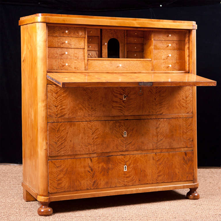 Swedish Karl Johan Biedermeier chest of drawers in book-matched fire birch veneer with fall-front secretary opening to reveal seventeen small drawers and a central cubby whose fascia are all in burled olive wood with turned pulls. Nine interior