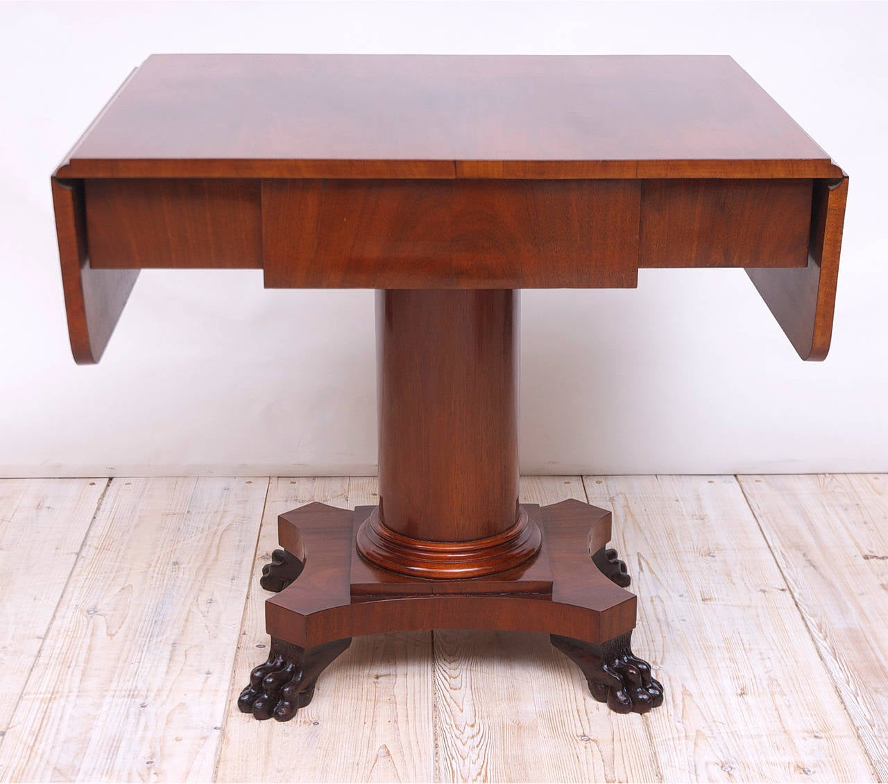 A handsome Biedermeier sofa table or writing desk in Cuban mahogany with one drawer and two drop leaves on cylinder column resting on quatre-form base with carved lions' paw feet, Sweden, circa 1840-1850.