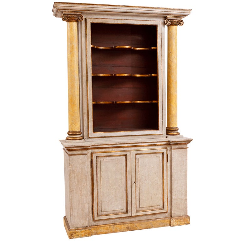 A very beautiful and tall Italian neoclassical style cabinet with polychromed finish, with open display shelves over base with two doors. This impressive cabinet is very dramatic with its faux-marble columns and carved ionic capitals, Italy, late