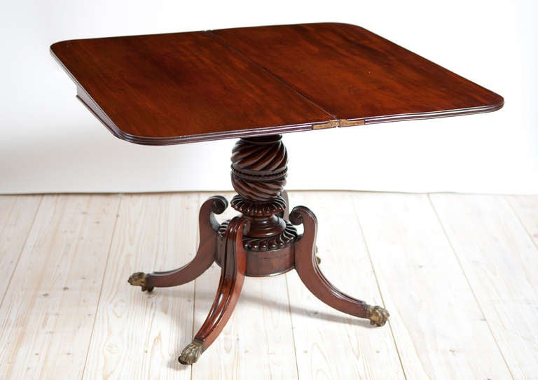 American federal game table with beautifully articulated carving, Boston, circa 1815. Combination of crotch mahogany veneer on the apron and solid mahogany top, centre column and legs terminating in original brass lion paw casters. Original hinges