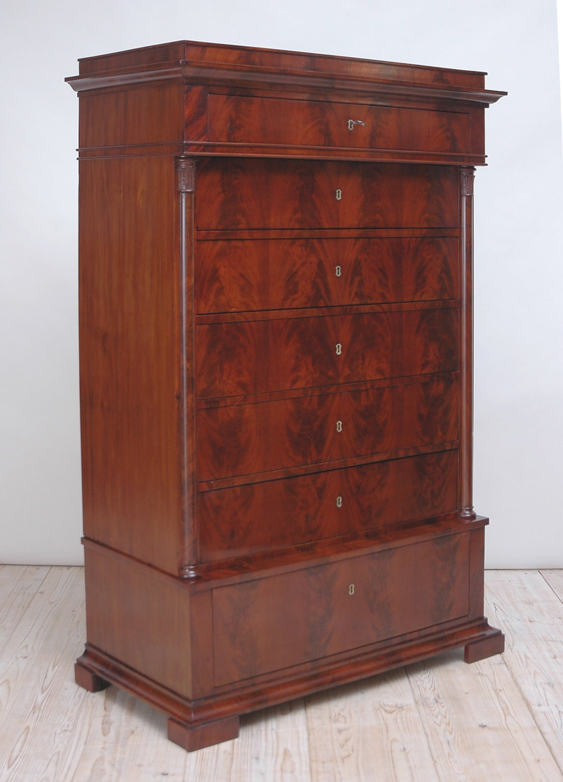 A handsome late Empire or early Biedermeier tall chest on chest with seven drawers and pedestal top. Middle section is flanked by split-turned columns with well-articulated palmette carvings on the capitals. Features beautiful book-matched, crotch