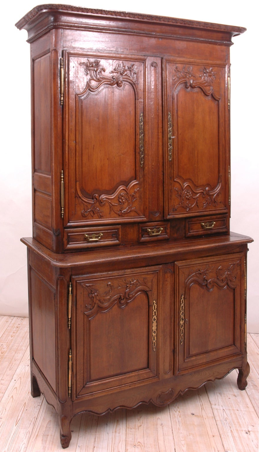 A lovely French buffet a Deux Corps (in two parts) from Normandy, France. Offers carved embellishments of cornucopias, flowers and foliage on the upper and lower cabinet doors, with carved apron and scroll feet. Original brass hinges, key escutcheon