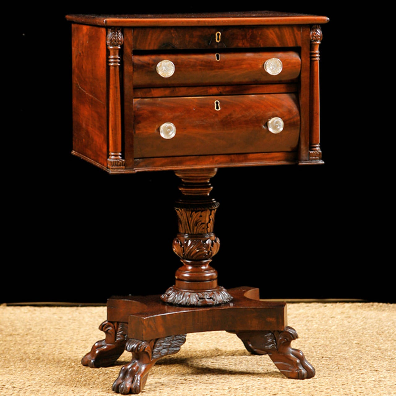 A fine Empire work table in mahogany on foliate-carved, baluster-turned pedestal resting on quatre-form base and terminating with winged carved lions' paw feet. Top opens to baize-lined writing surface over two drawers with beveled glass pulls.