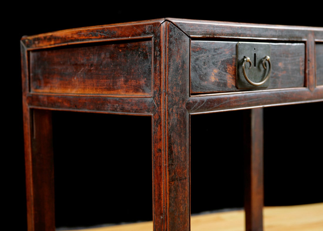 A handsome Chinese table in elm with a rich patina showing original cinnabar lacquer finish. Table offers two drawers and bottom shelf. A metal coin slot that lines up with right drawer is visible on the top, Qing Dynasty, circa 1790. Measures: 47