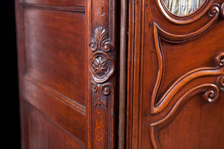 French antique Louis XV Armoire in walnut with glass panels. A fine and impressive armoire whose wood exhibits a beautiful patina, France, mid-1700s. Glass panels, while handblown, were more than likely added at some point in the armoire's
