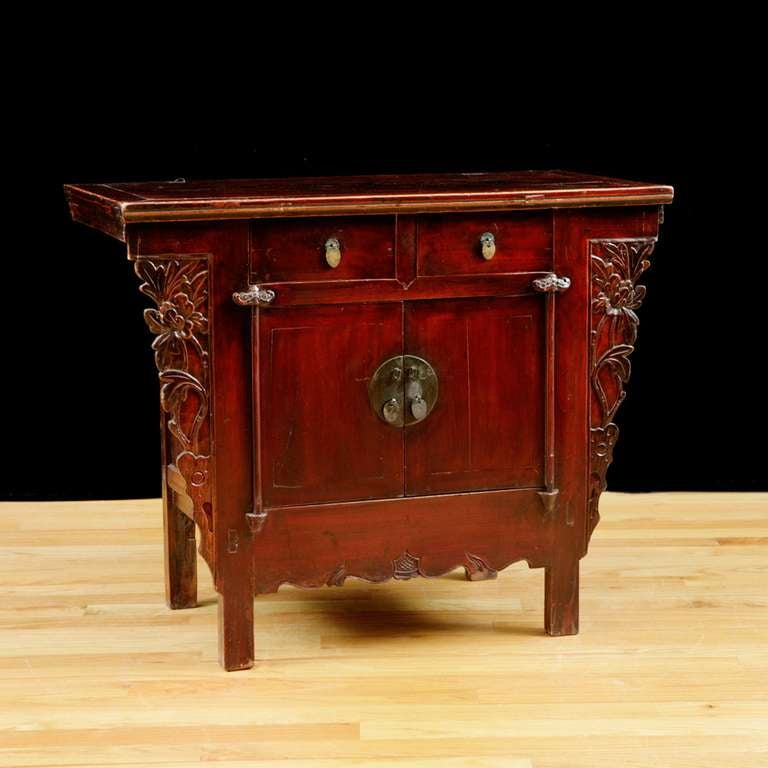 """Chinese provincial red lacquered elm Cabinet from the Qing dynasty. In original lacquer with carved peonies on side spandrels. Measure: 40"""" wide x 20 ½"""" deep x 33"""" high."""