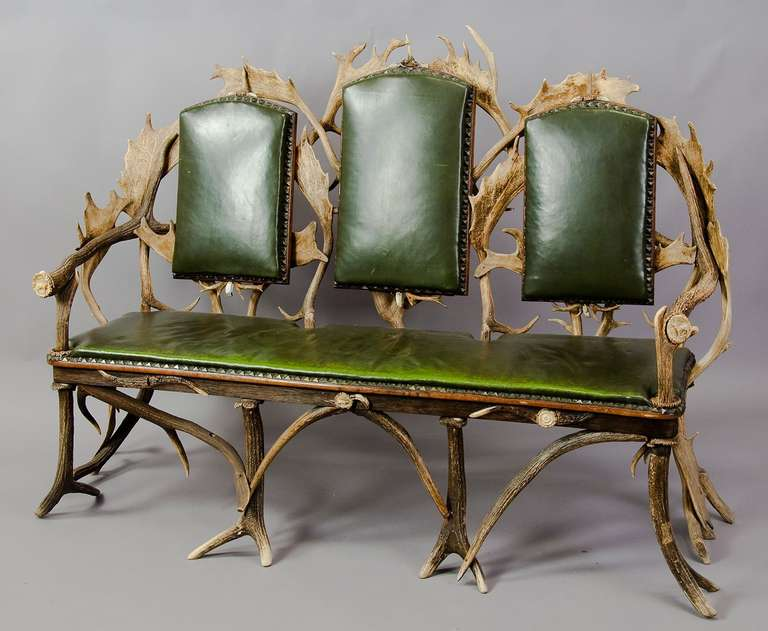 An antler sofa with three seats, made of antlers from the deer and fallow deer. Decorated with figural carved horn roses. Green leather cover.