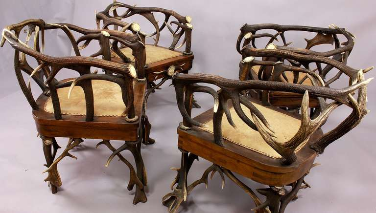 A set of four antique Black Forest antler armchairs, made of horns from the stag and fallow deer. Decorated with turned and figural carved horn roses. Upholstered seat with leather cover. Executed circa 1900.