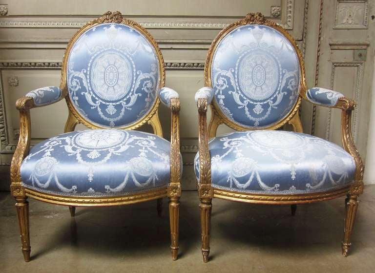 Pair of French Louis XVI style armchairs with a gold leaf finish from the late 19th century. These fauteuils are beautifully carved with gadrooning, flutted legs and a ribbon at the crest of the oval back. The gilt wood finish has a lovely old