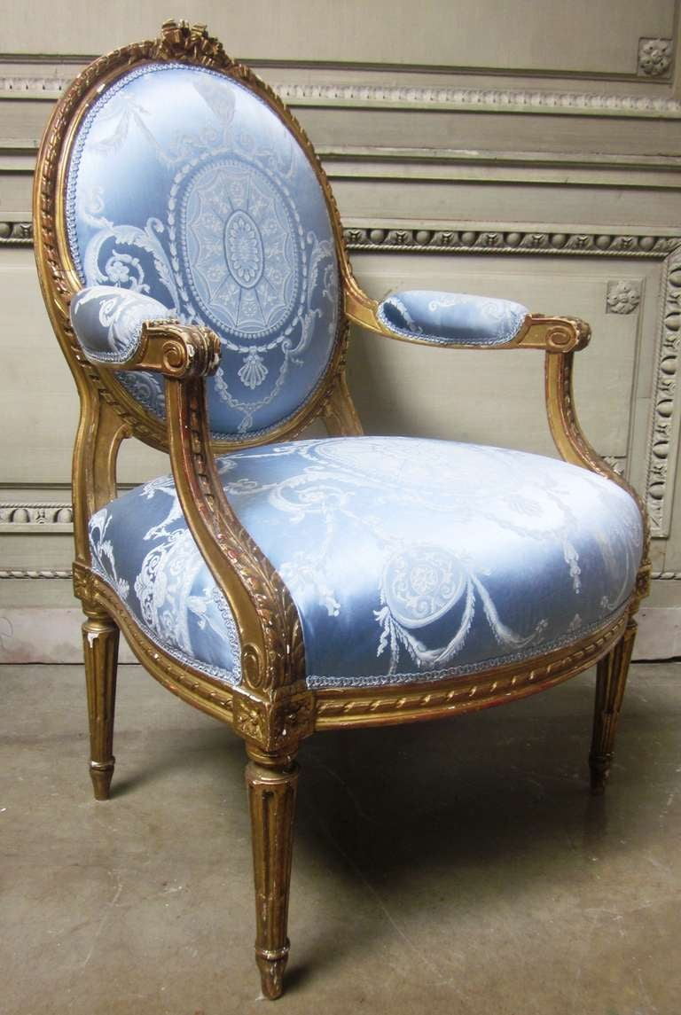 Carved 19th Century Pair of French Louis XVI Style Armchairs with a Gold Leaf Finish For Sale