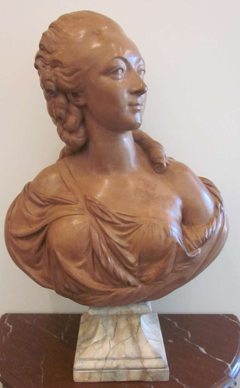 A French terracotta bust of Madame du Barry on a faux marble stand. This is a 19th century copy of the 1773 sculpture by Augustin Pajou. The original resides in The Louvre Museum in Paris.