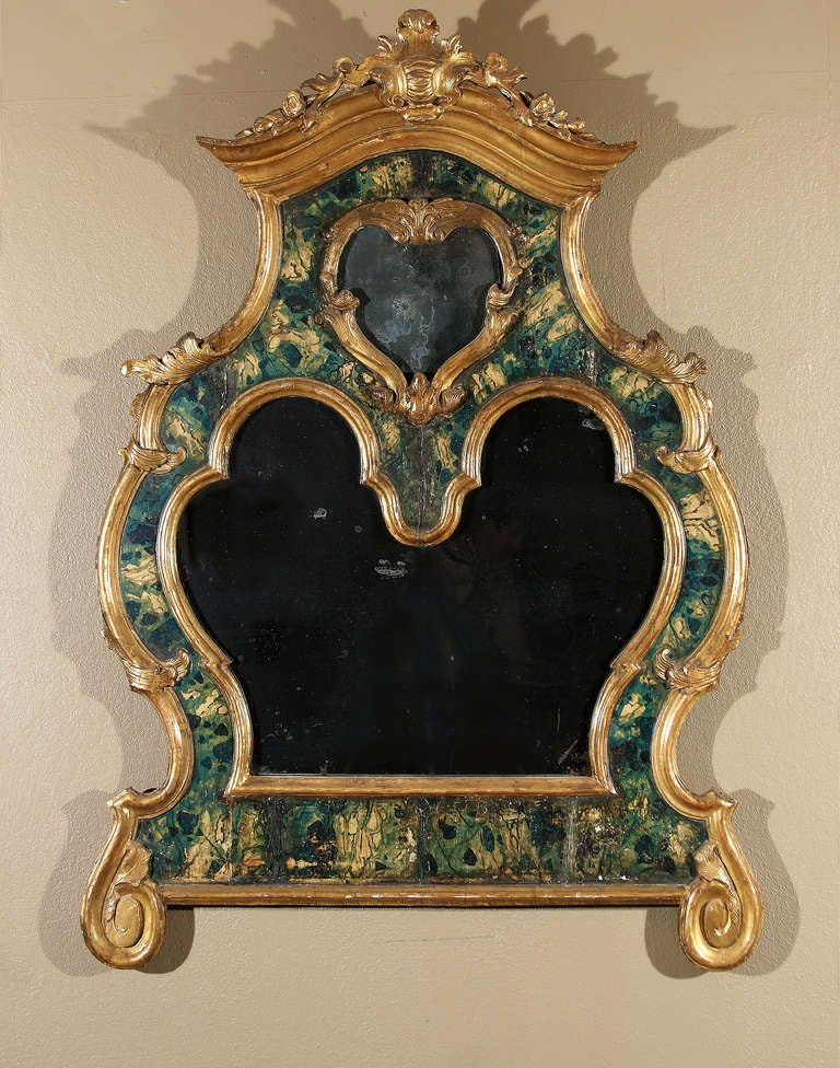 An exuberant Italian Rococo mirror with parcel-gilt and faux marble and a double mercury plate glass. Minor distressing to faux marble.