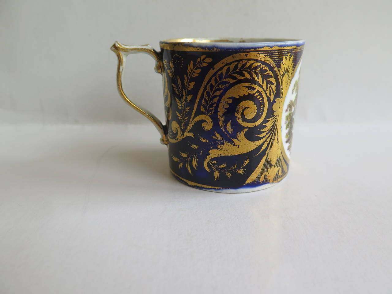 This is a highly collectable porcelain Coffee Can or cup with a hand painted scene called