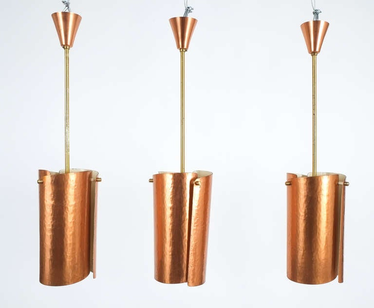 Beautiful set of three copper pendant lights from Italy with curved and hammered copper sheets. One bulb each with 60W max. The brass rods may be shortened or customized or replaced at will. Priced and sold individually.