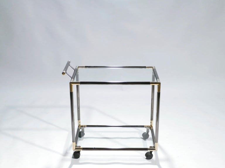 The designer of this pair of gunmetal and brass bar cart aimed to emulate the simple structure and visual drama of Maison Jansen's iconic style. Sleek lines and an ordinary rectangular structure are offset by bright brass joints at all four corners.