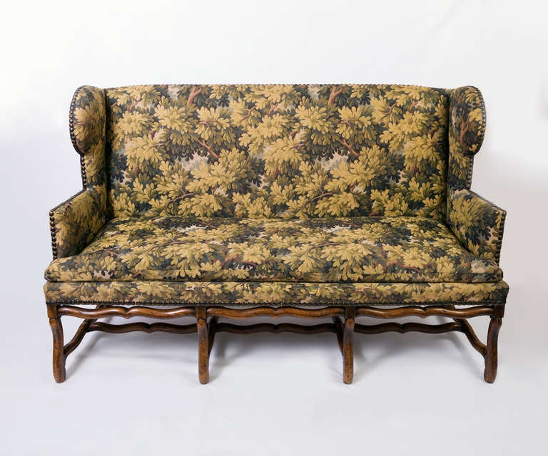 This is a 19th century mouton 4 stretcher sofa with cross stretchers. The French sofa has upholstered arms and nailhead trim. It is covered in tapestry fabric. The sides have a winged detail on each side finishing in a flat arm.   It is very