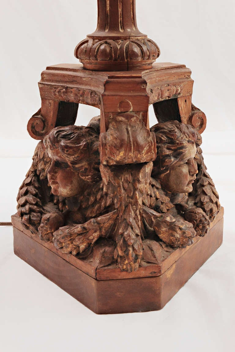 This 19th century carved wood Italian lamp with three cherubs at the base. This Italian Cherub carved lamp was originally a candelabrum that has been electrified. Beautiful custom shade with gold cord trim and waxed drip candle.