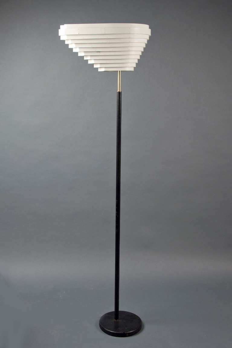 """White enameled metal, vented roughly conical shade on a black leather sleeved brass shaft, impressed with maker's mark; from Aalto's (1898-1976)""""Angel Wing"""" series, model A805. Literature: H. Cantz's Alvar & Aino Aalto Design, Angel Wing examples"""