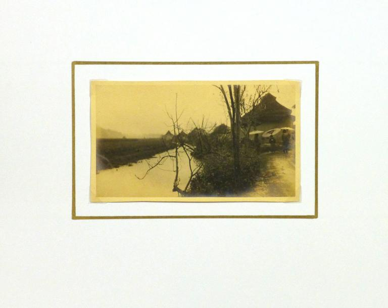 Vintage pictorialism albumen photograph of female figures with their parasols outside a small Japanese village, circa 1920.   Original artwork on paper displayed on a white mat with a gold border. Archival plastic sleeve and Certificate of