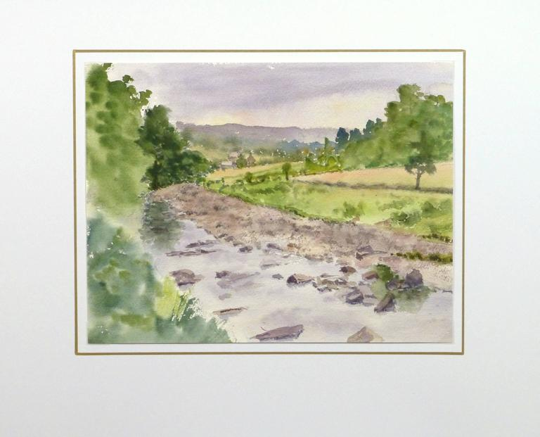 English watercolor of a shallow creek winding through green pastures by artist M. Powell, circa 1990.   Original artwork on paper displayed on a white mat with a gold border. Archival plastic sleeve and Certificate of Authenticity included. Artwork,