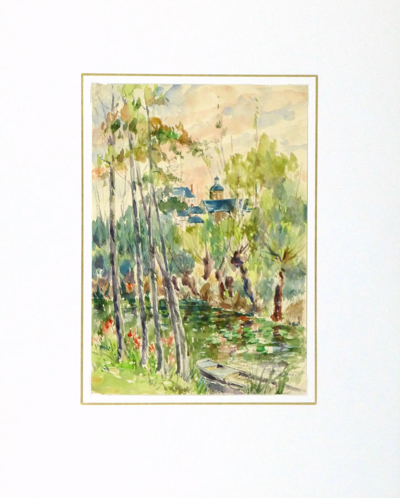 Lively French watercolor of peaceful country tranquility along the river bank while town buildings peep out by artist Roger Tochon, circa 1930.  Original vintage one-of-a-kind artwork on paper displayed on a white mat with a gold border. Mat fits