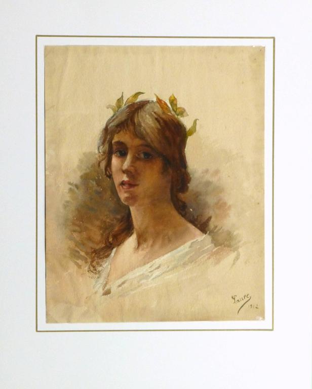 Warm and pleasing watercolor portrait painting of a charming young lady with a small crown on leaves accenting her hair, 1912. Signed Laure and dated lower right.  Original one-of-a-kind artwork on paper displayed on a white mat with a gold border.
