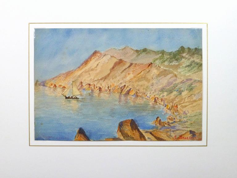 Bright watercolor landscape of a sailboat drifting in a small cove ringed by red rock mountains by artist M. Balestié, circa 1930. Titled lower left and signed lower right.  Original one-of-a-kind artwork on paper displayed on a white mat with a