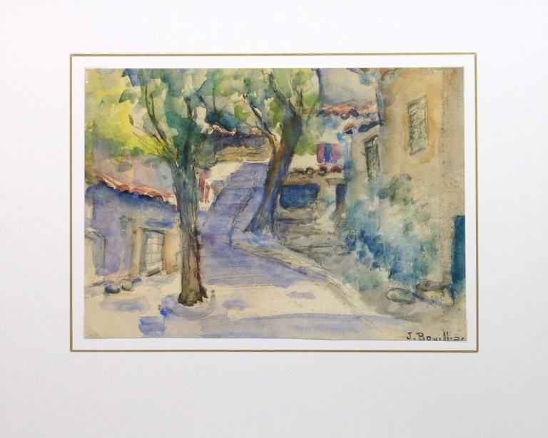 Inviting watercolor of a small path winding through a quaint town using soft, cool hues by artist Jacques Bouillac, circa 1950. Signed lower right.  Original one-of-a-kind artwork on paper displayed on a white mat with a gold border. Mat fits a