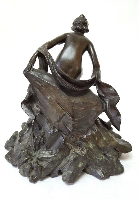 """An original Art Nouveau Period bronze sculpture in the manner of Alphonse Mucha (1860-1939) titled """"Water Nymph"""", c. 1890. This is a stunning bronze; a lady stepping down from the rock into the water. There is a frog to her lower right."""