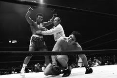 Muhammad Ali victorious, getting held back by referee Mark Conn after knockdown