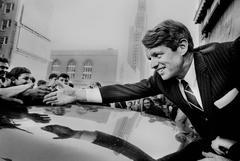 Bob Kennedy reaching hand over car, Brooklyn, New York