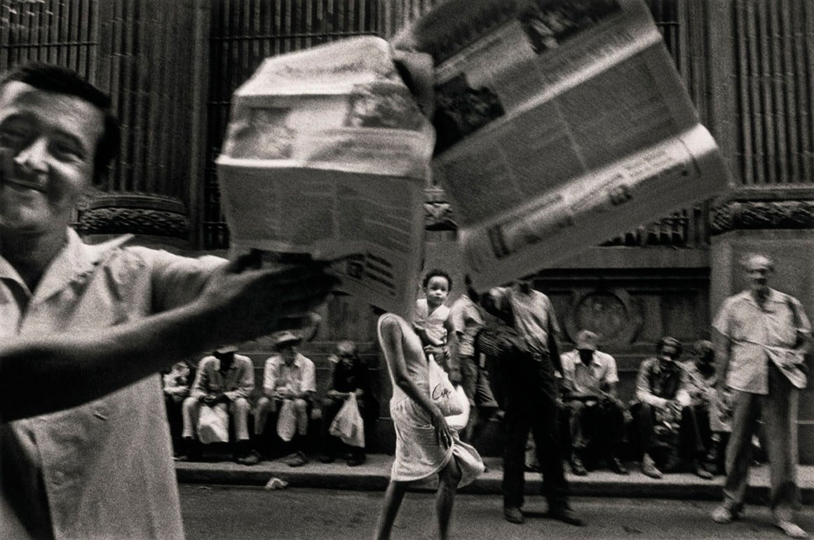 Ernesto Bazan Figurative Photograph - Man selling Granma newspaper, Havana