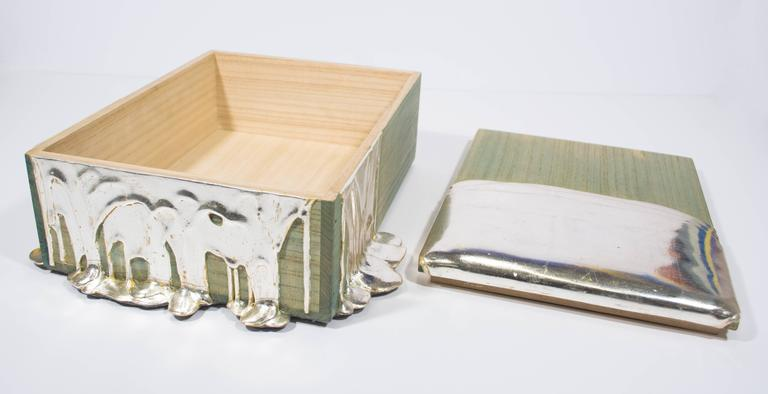 This box by Nancy Lorenz features a pawlonia box traditionally used for Japanese tea service. To create the effect of poured molten gold, Lorenz builds up layers of gesso, brushstroke by brushstroke, and then covers that with silver leaf.   Nancy
