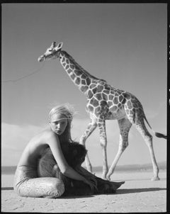 Blond Model sitting shirtless  on the desert hugging a monkey from a giraffe