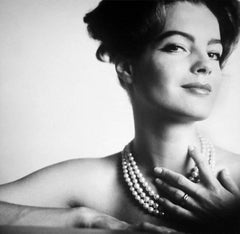 portrait of romy schneider, almost naked only with a pearl necklace touching her