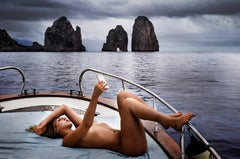 Capri Selfie - blonde naked woman on a boat, lying on her back, making a photo