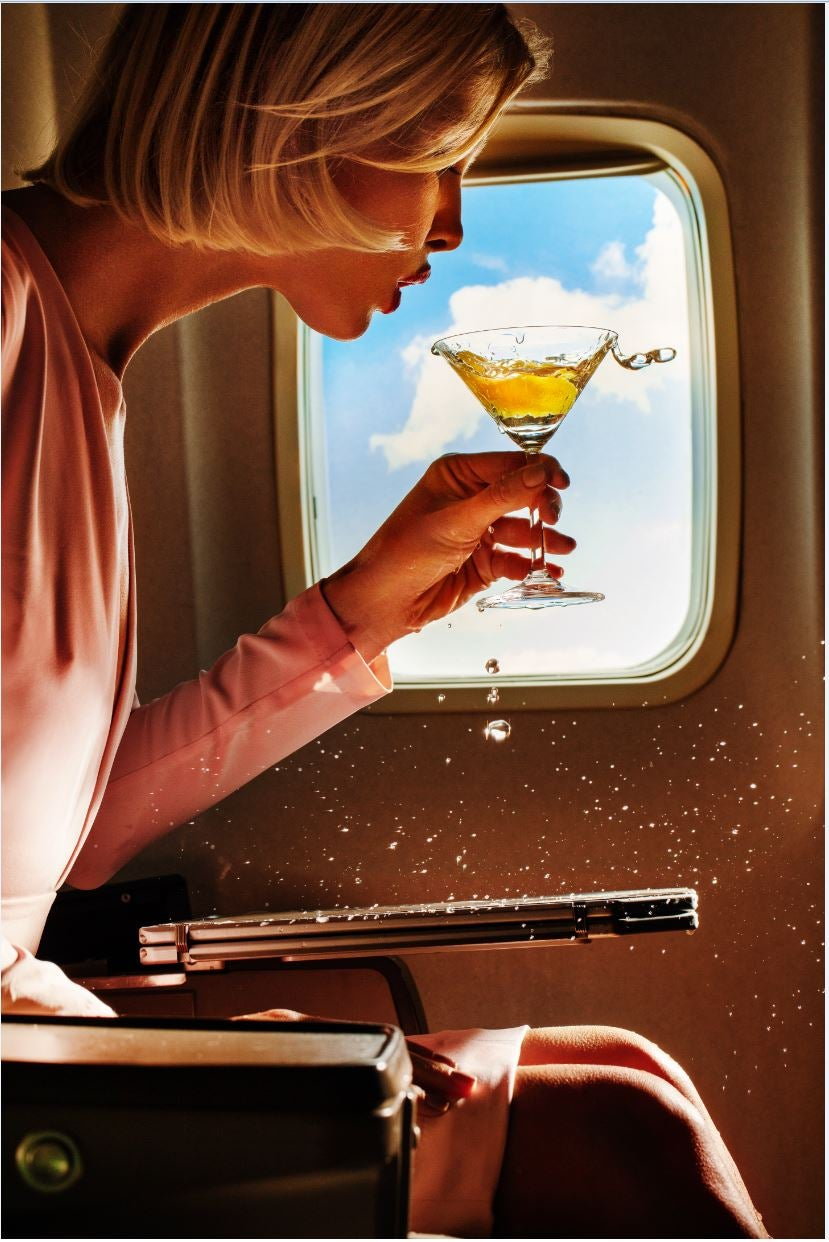 Turbulence - portrait of a model spilling champagne in an airplane