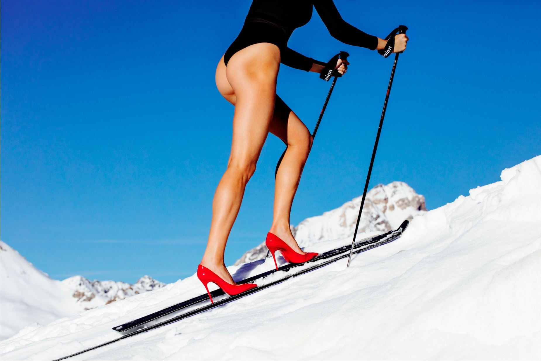 Ski Patrol II - model skiiing with high heels and mountains in the background