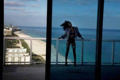 Recap- Woman in black lingerie with a jacket, standing on the balcony at the sea