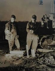 Untitled (two men lowering dynamite)