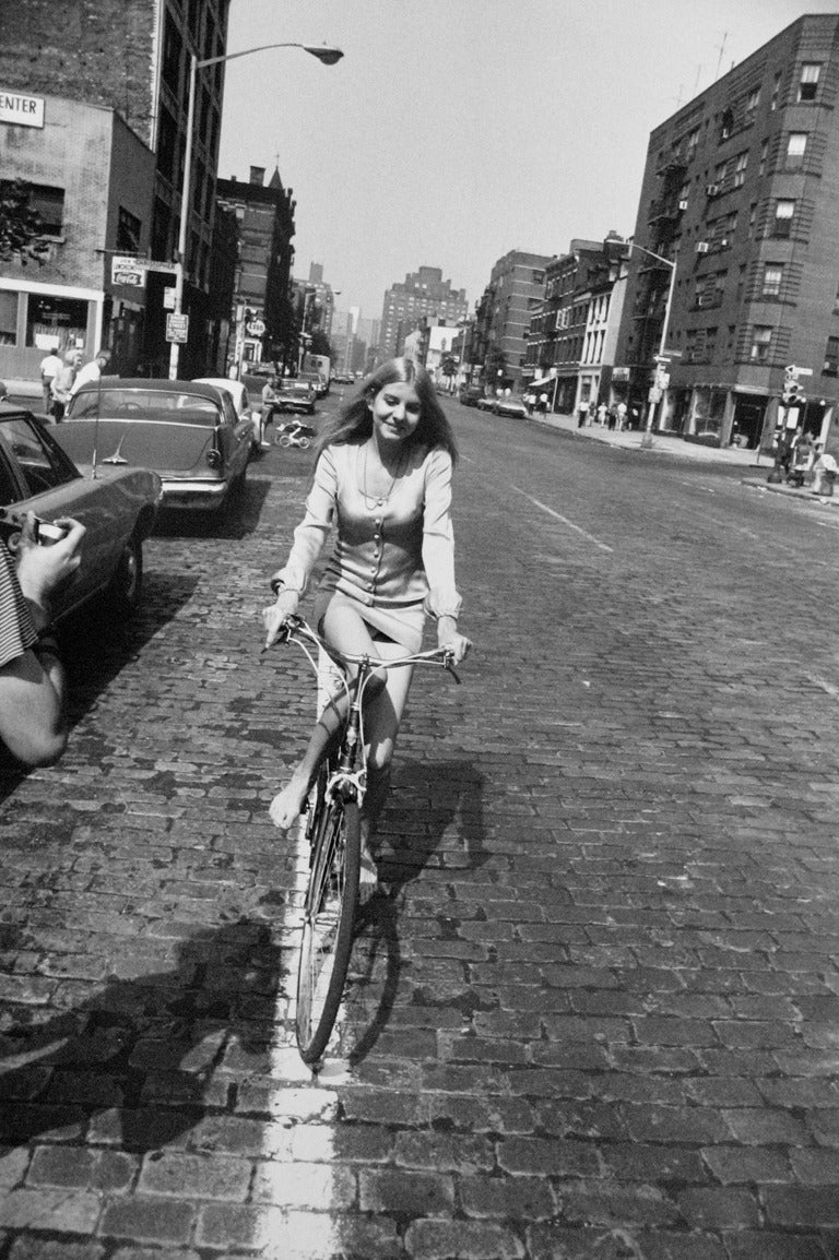 Garry Winogrand Black and White Photograph - Woman Riding Bicycle, From the Women are Beautiful Portfolio