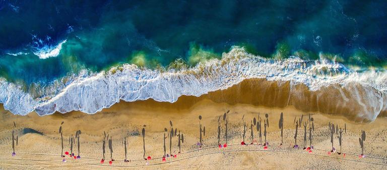 Beach photography, shadows of people walking on the beach with umbrellas