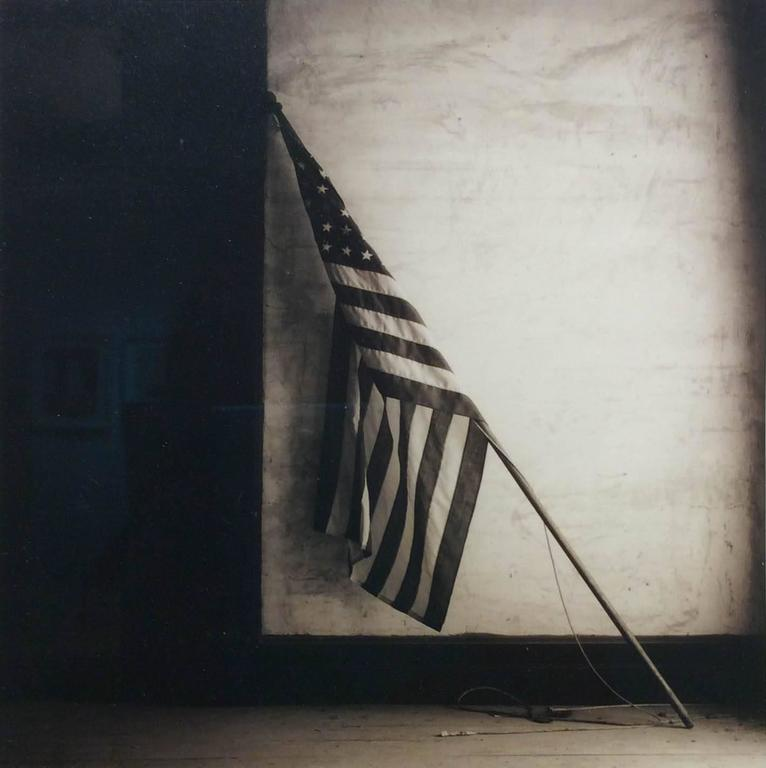 American Flag (Square, Sepia Toned Vintage Flag Leaning Against White Wall)
