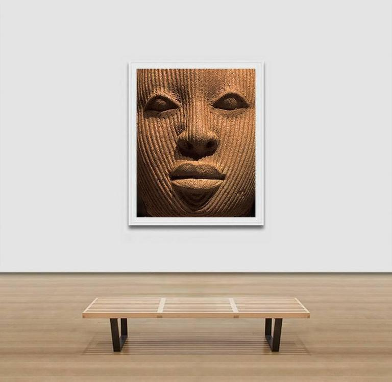 """Pierre Sernet's F019, Nigerian, Terracotta is a Large 61 x 50 inches Giclée Print. It is framed. The image is a close-up photograph of a sculpture from a Nigerian Terracotta, only the face can be seen. The artwork is part of the """"Face"""" series, where"""