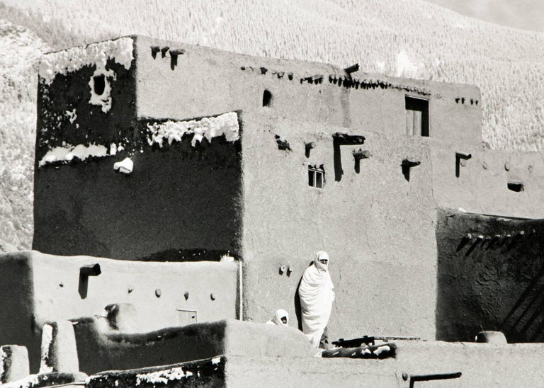 Original signed framed black and white photograph by Myron Wood (1921-1999) of Taos Pueblo, New Mexico with mountains in the background. Presented in a custom frame, outer dimensions measure 13 ¼ x 16 ½ x ½ inches.  Image size is 6 ¼ x 9 ½