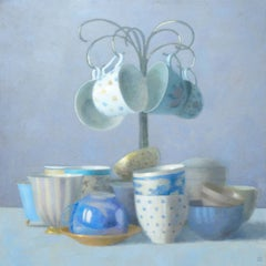 FOUR TEACUPS HANGING, cups hanging above other cups on table, crowded table