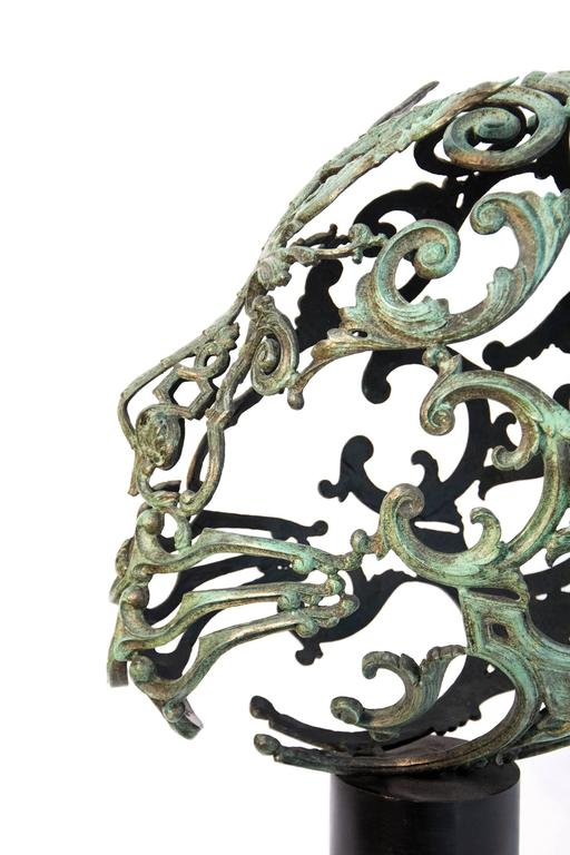 Bronze head fashion from cast found objects - the decorative elements added to furniture early in the last century.  Bronze sculptor Dale Dunning's skilled craftsmanship never overshadows the story he wants to tell. Often he presents new ways of