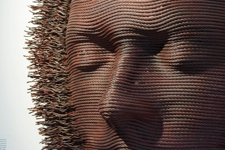 Wall hanging sculpture, created using steel cable. It is finished with a rich patina.  Sculptor Dale Dunning's skilled craftsmanship never overshadows the story he wants to tell. Often he presents new ways of looking at the human face – sometimes